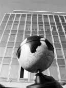 Fotosymbolik: Globus mit schwarzen Flecken vor Konzernhochhaus.