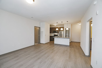 Living room with light wood flooring, white walls, doors to bedrooms on left wall and right wall, looking into kitchen with an island