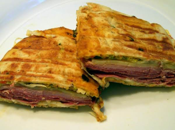 Muffaletta With Layers Of Delicious Ham, Salami, Provolone, Mortadella,fontina And Olive Salad . Pressed Into A Naan Paninni.