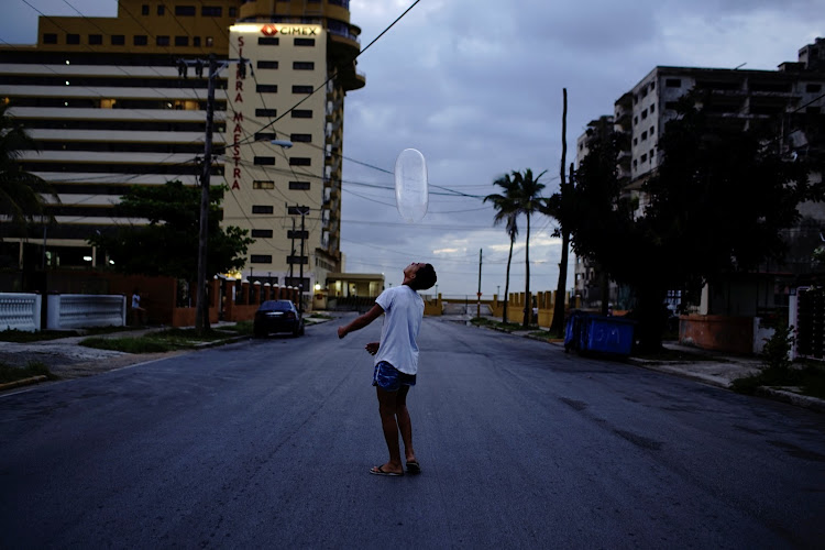 Arturo Perez, 14, plays on the street with a condom in Havana, Cuba, last month.