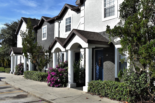 Exterior of apartment townhomes with blue doors, white pillars, grey brick, and white stucco walls