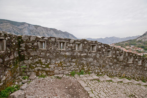 Kotor-battlement.jpg - A medieval battlement, with narrow slits for weapons, along the 1,350-step trail rising above Kotor.