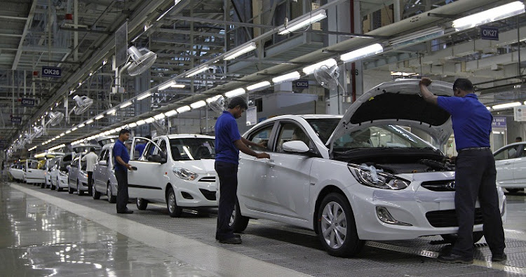 Workers assemble cars inside the Hyundai Motor India Ltd. plant in the southern Indian state