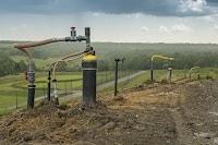 Pumpen auf einem Feld und ein weites grünes Tal im Hintergrund