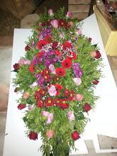 Photo: composition funéraire raquette de deuil fleurs utilsées: roses (environ 50 fleurs), germinis(environ 20 fleurs), alveolés (chrysanthemes) de plusieurs couleurs (15 tiges de fleurs ) prix: 120 euros environ