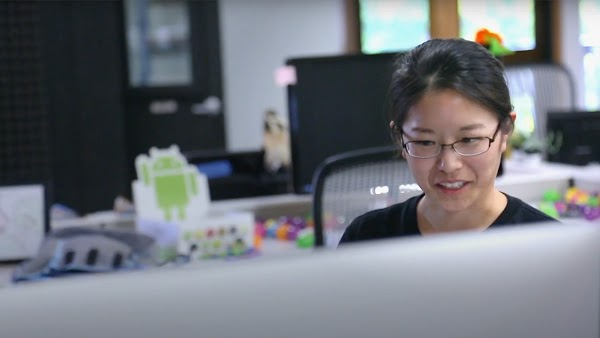 Asian woman wearing glasses sitting in front of a computer in an office.
