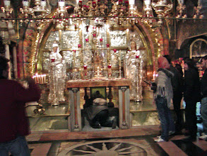 Photo: Tourists bend to touch the Rock of Calvary in the Greek Orthodox Calvary.  This is considered the site of the 12th Station--Jesus dies on the Cross.