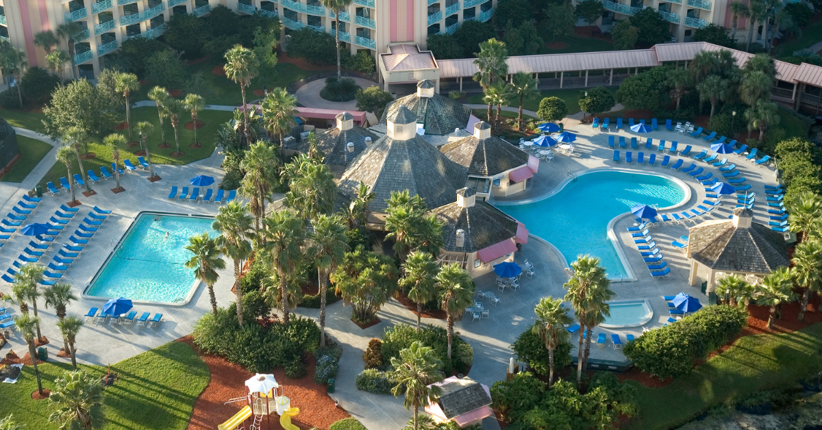 A resort with several swimming pools and green areas