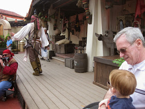 Photo: Day 4 - Watching the Pirates stage show with Captain Jack Sparrow. Richard Josiah wasn't sure what he thought about a real life pirate in front of him and liked the security of Papa's lap :-)