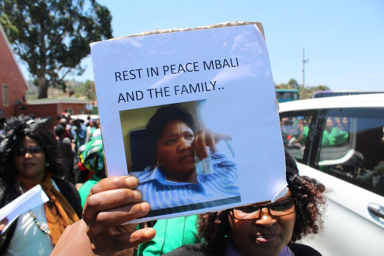 A mourner waves a placard at the funeral of seven members of the Khoza family who were murdered in Vlakfontein, south of Johannesburg.