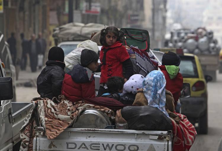 SEEKING REFUGE: Syrian children sit on the back of a pickup truck leaving the city of Aleppo, seeking an escape from the conflict zone. Picture: REUTERS