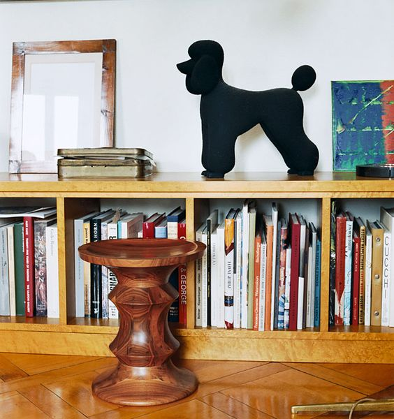 the one piece walnut stool next to a bookshelf