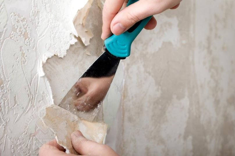 Zrywanie starej tapety ze ściany.