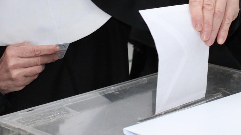 Un votante deposita su sobre en la urna
