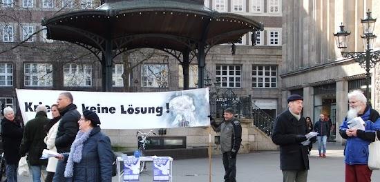 Infostand. Menschen mit Flugblättern, Transparent: «Krieg ist keine Lösung!».