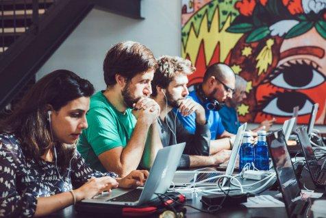 Team members working on their laptops