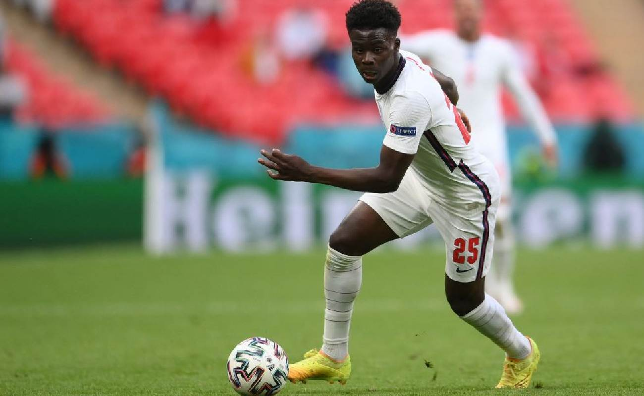Alt: Bukayo Saka on the ball for England - Photo by LAURENCE GRIFFITHS/POOL/AFP via Getty Images