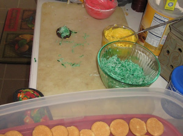 In each of two custard cups put some frosting.  Dye one batch yellow...