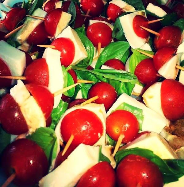 To assemble the cherry tomato skewers: Using a toothpick:  Put half of a cherry tomato...