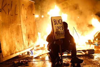 Photo: REFILE - CORRECTING HEADLINE  A demonstrator sits in front of a street fire during a demonstration following the grand jury decision in the Ferguson, Missouri shooting of Michael Brown, in Oakland, California November 25, 2014. The grand jury decided on Monday not to indict a white police officer over the fatal August shooting of an unarmed black teenager.  REUTERS/Stephen Lam  (UNITED STATES - Tags: CIVIL UNREST POLITICS CRIME LAW TPX IMAGES OF THE DAY)
