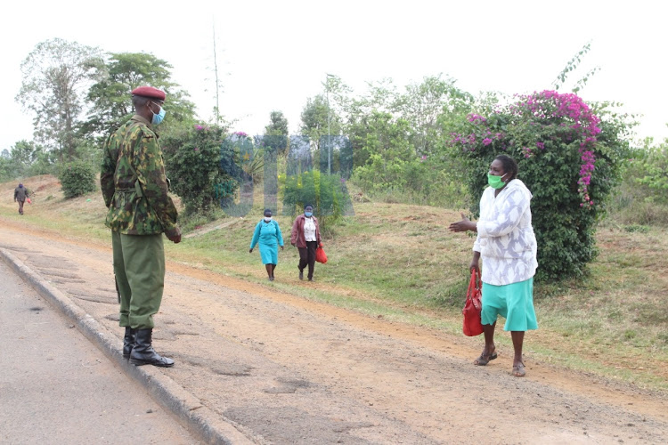 Travelers walk past a police roadblock at a checkpoint meant to indicate border of Kiambu and Murang'a counties in BluePost area, Thika on March 27, 2021