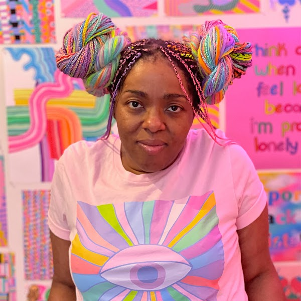 Portrait of artist with multi-colored individual braids in two buns wearing a pink shirt in front of their work.