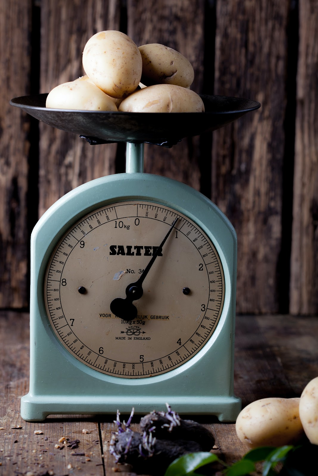 Potatoes rest on a turquoise produce scale. which reads at just under one pound.