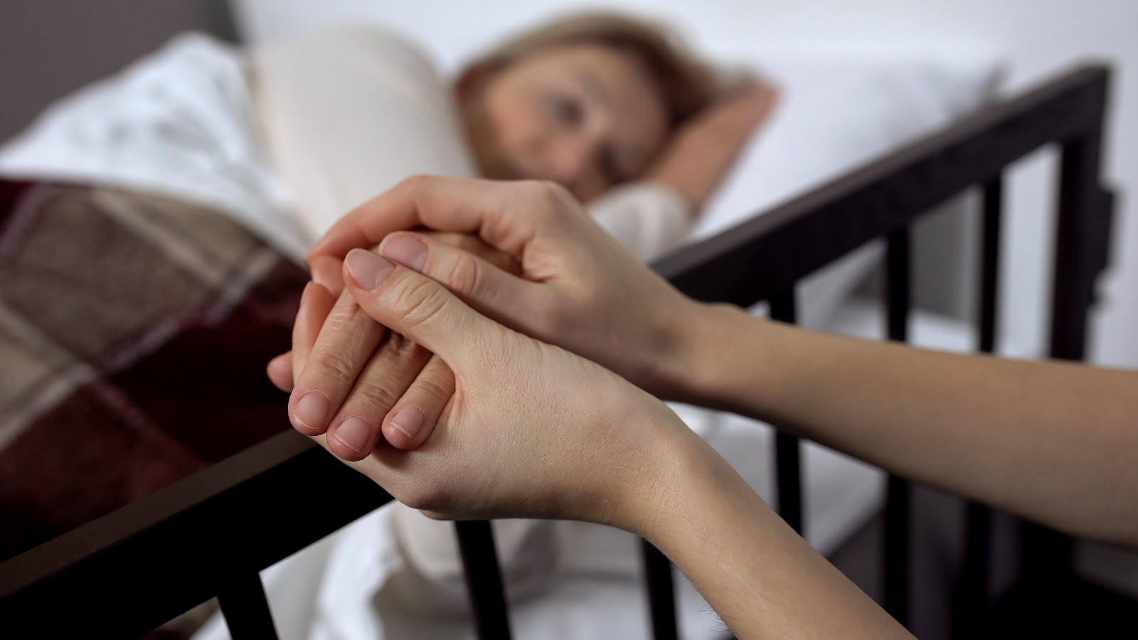 Holding the hands of a patient in a sick bed