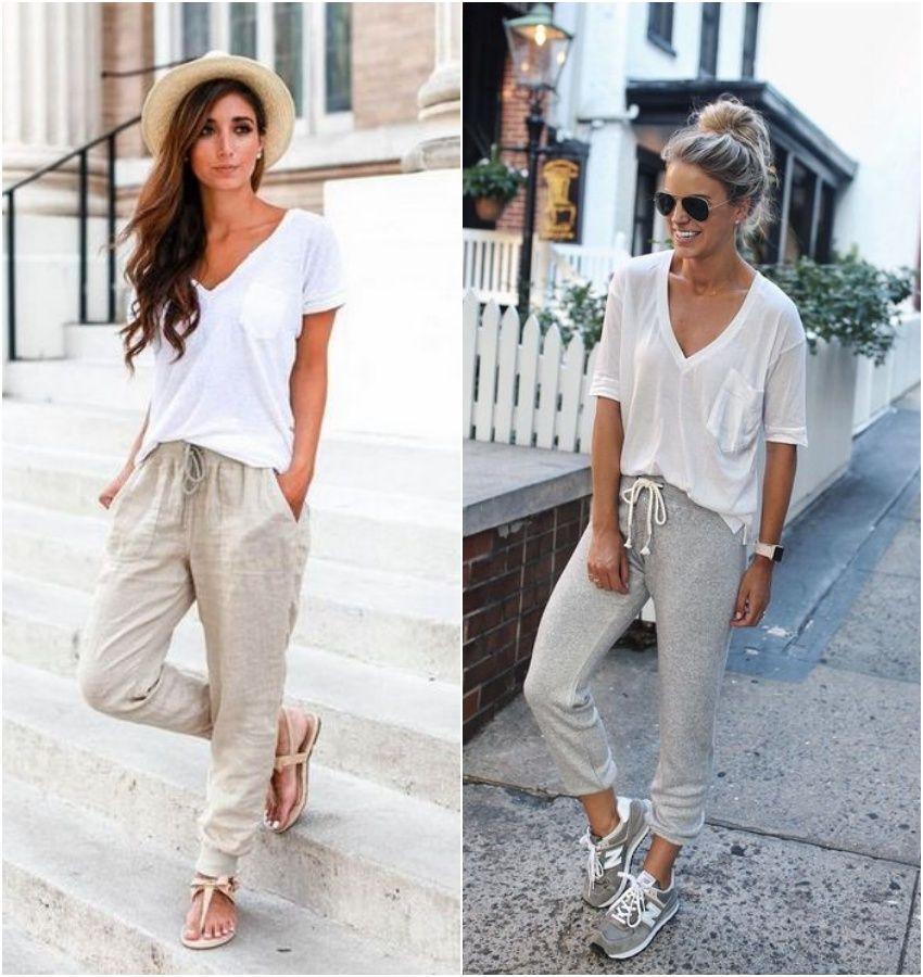 Na imagem há duas mulheres brancas vestidas com camisetas brancas e calças acinzentadas modelo jogger.