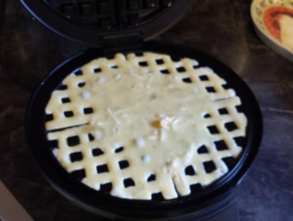 Preheat the waffle iron. Brush all surfaces with oil or butter. Pour half the...