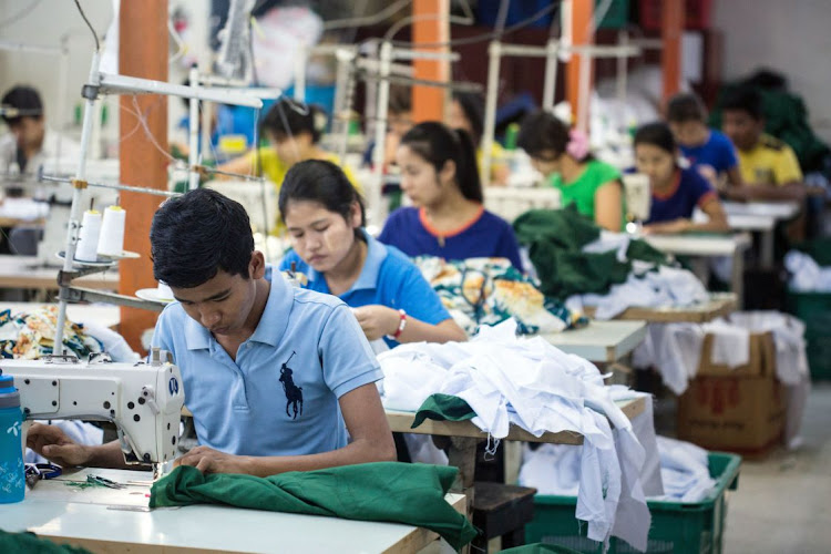 Workers use sewing machines to manufacture shirts at a factory in Yangon, Myanmar. Picture: TAYLOR WEIDMAN