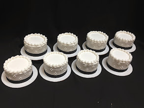 Photo: Individual wedding cakes for centerpieces. 4-dot clusters w/black ribbon wrap & traditional border on each.