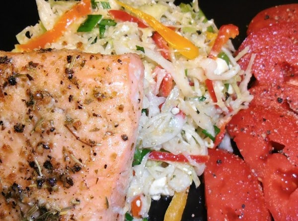 plate coleslaw and top with salmon fillets. drizzle the olive oil and butter on...