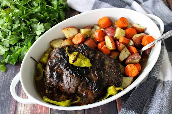 Slow Cooker Mississippi Roast In A Roasting Dish With Vegetables.