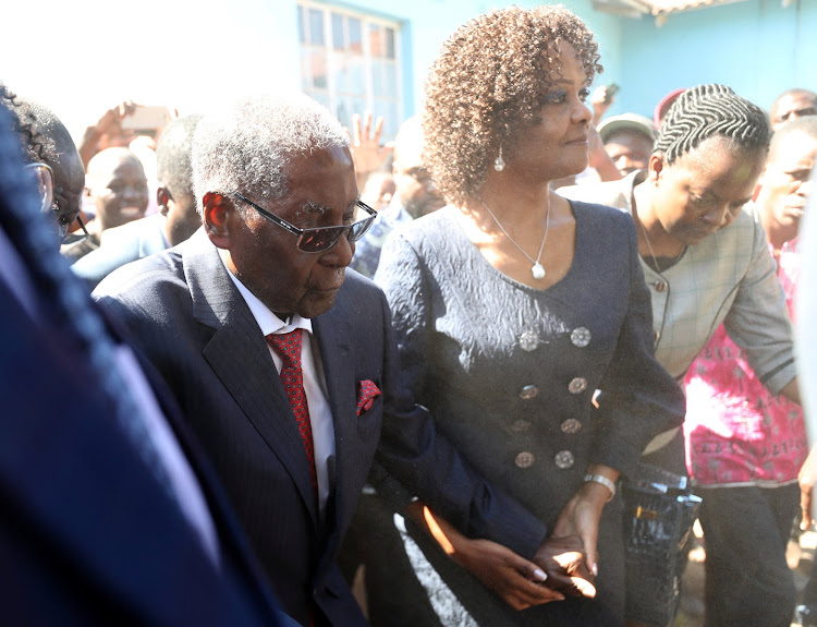 Dust engulfs former Zimbabwean president Robert Mugabe and his wife Grace as they arrive to vote in the general elections in Harare, Zimbabwe on July 30 2018.