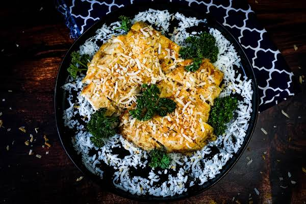 A Platter Of Grilled Coconut Chicken With Toasted Coconut On Top.