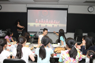 Photo: Dance class students enjoying their last school day with a little party while reviewing their performance videos.