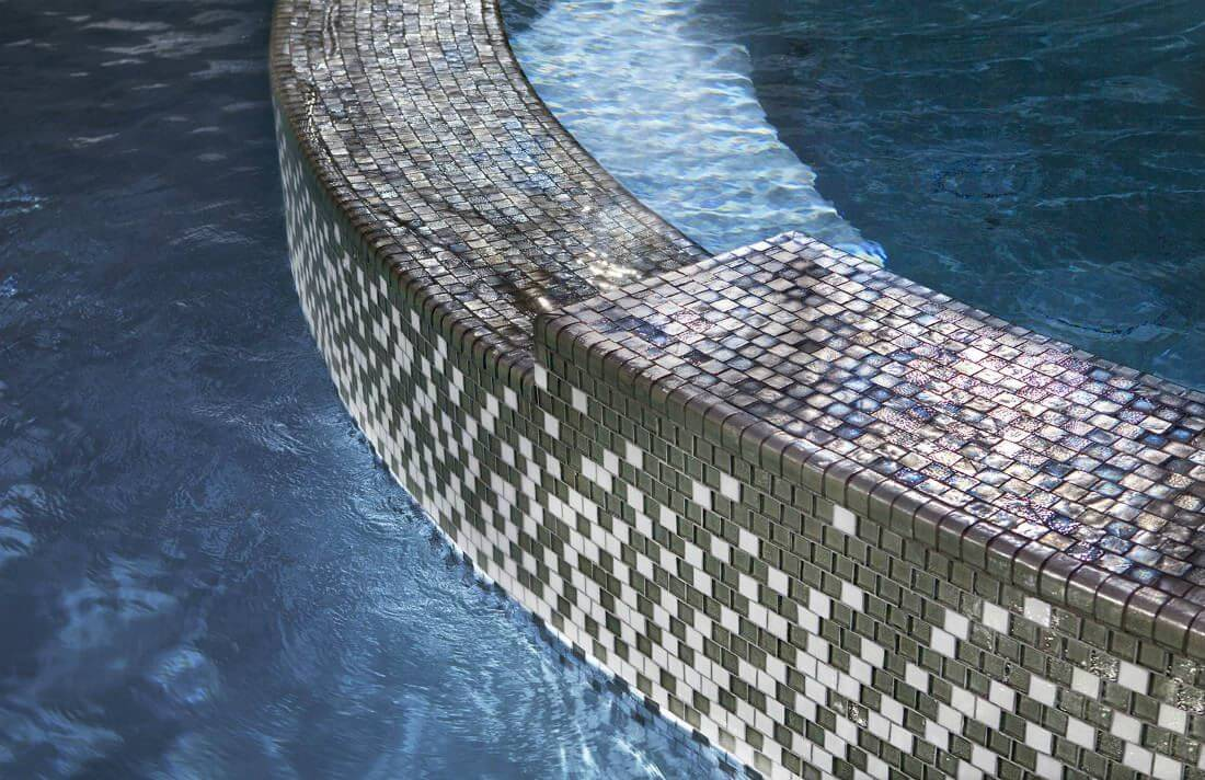 Iridescent gray and white mosaic tile grid in a swimming pool