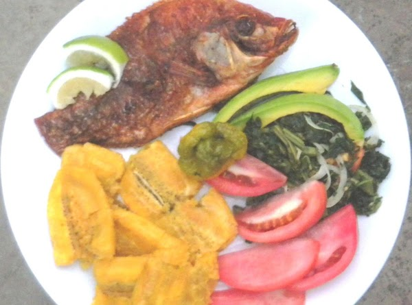 Vanillated lemon zest fried fish garnished with lemon slices and served with steamed callaloo, avocado, salad tomatoes and fried, crushed green plantains.