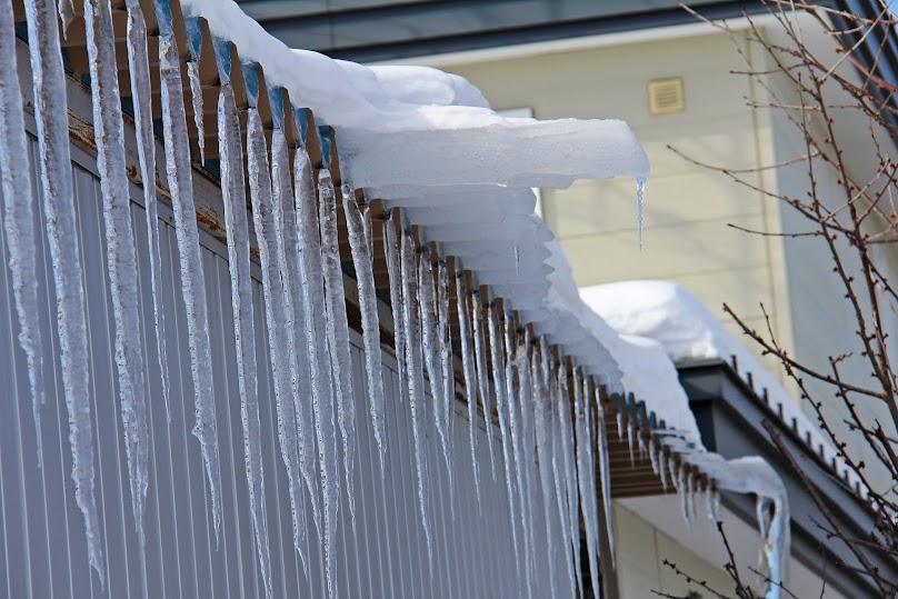 Ośnieżony dach płaski z soplami lodu