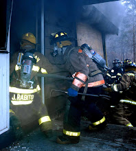 Photo: Norm Cummings SPECTRUM/Sherman firefighter J. Rabito and others enter a burning building as part of Jan. 13, 2007 drill  at Mill Pond in Sherman