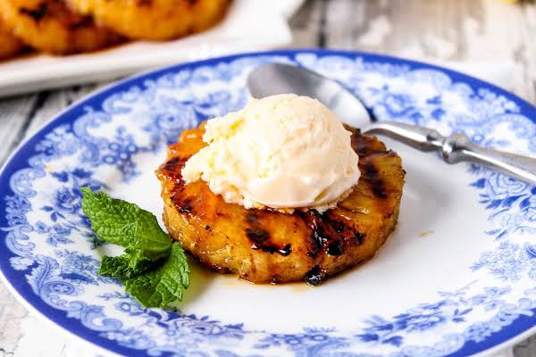 Orange Glazed Grilled Pineapple On A Plate With A Scoop Of Vanilla Ice Cream.