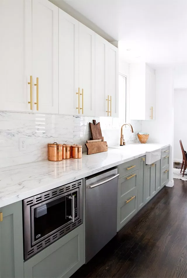 contrasting jade green and white cabinets are complemented by a white marble countertop and backsplash. Gold cabinet hardware is used for a contemporary look