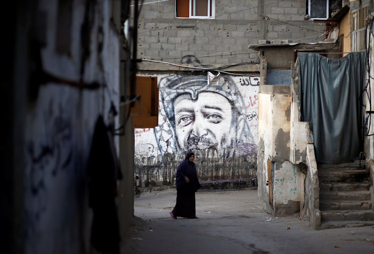 A Palestinian woman walks past a mural depicting late Palestinian leader Yasser Arafat on a wall at Al-Shati refugee camp in Gaza City earlier this month.