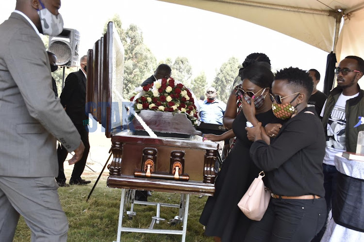 Ruth Matete and her best friend Angie Kabura stand next to Ruth Matete's husband's body at Lang'ata cemetery on July 23,2020