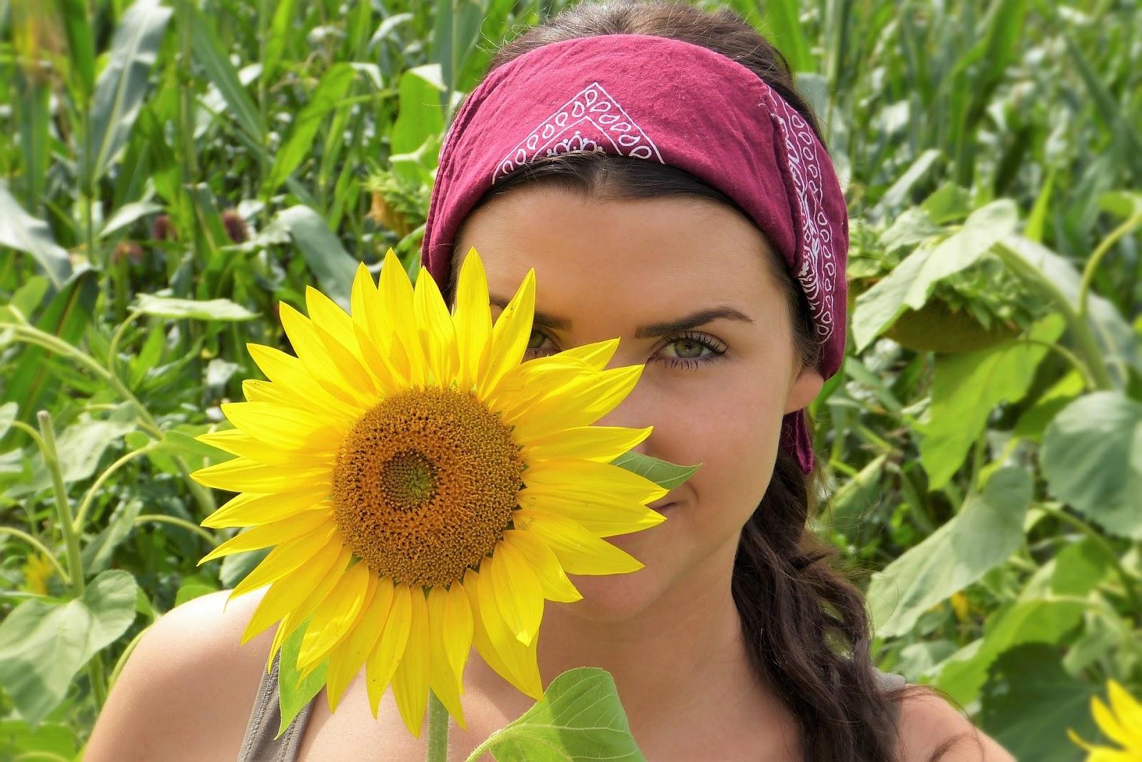 Woman peeking from behind sunflower blossom