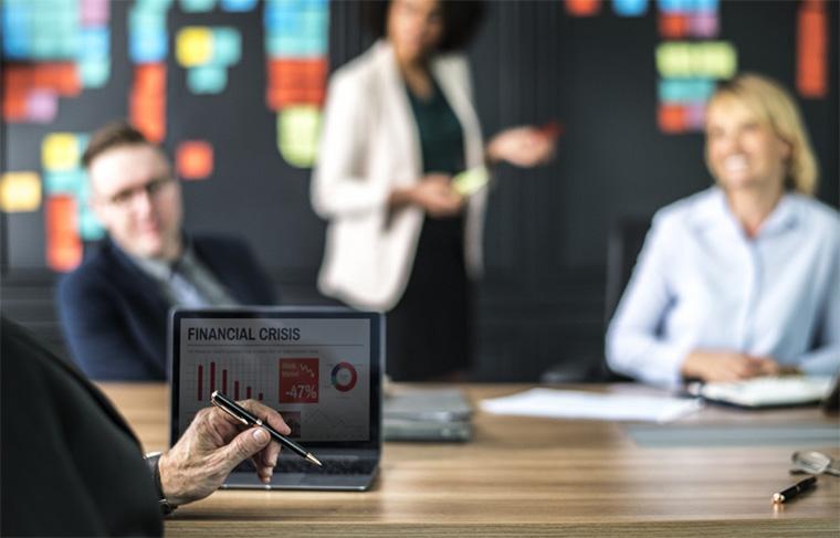quatro pessoas fazem briefing numa sala de reunião enquanto tela do notebook mostra gráficos de crise financeira