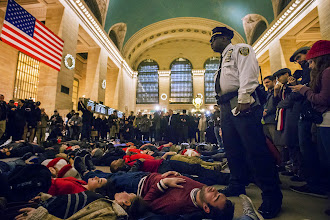 """Photo: ATTENTION EDITORS - REUTERS PICTURE HIGHLIGHT TRANSMITTED BY 2230 GMT ON DECEMBER 3, 2014    AAL101  A police officer stands over activists, demanding justice for the death of Eric Garner, as they stage a 'die-in' during rush hour at Grand Central Terminal in the Manhattan borough of New York on December 3, 2014. REUTERS/Adrees Latif    REUTERS NEWS PICTURES HAS NOW MADE IT EASIER TO FIND THE BEST PHOTOS FROM THE MOST IMPORTANT STORIES AND TOP STANDALONES EACH DAY. Search for """"TPX"""" in the IPTC Supplemental Category field or """"IMAGES OF THE DAY"""" in the Caption field and you will find a selection of 80-100 of our daily Top Pictures.    REUTERS NEWS PICTURES.     TEMPLATE OUT"""