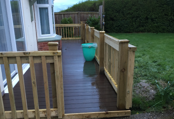 a wooden garden deck with wooden banisters