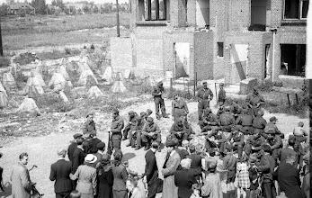 Photo: 0023. Goudenregenstraat bij de nrs. 257-255, links de Hanenburglaan. Geallieerde soldaten en burgers bij deels dichtgemetselde panden, kort na de bevrijding. Links asperges en prikkeldraad en een elektriciteitshuisje  http://www.loki-travels.eu/